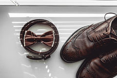 Brown bow tie, leather shoes and belt. Grooms wedding morning. Close up of modern man accessories Royalty Free Stock Photography