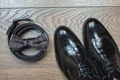 Brown bow tie lies on a belt, leather shoes. Grooms wedding morning. Wedding accessories. Brown bow tie lies on a belt, leather shoes on a wooden floor. Grooms Stock Photography