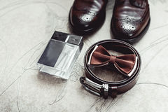 Brown bow tie, perfume, leather shoes and belt. Grooms wedding morning. Close up of modern man accessories. Look from above Stock Photo