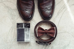 Brown bow tie, perfume, leather shoes and belt. Grooms wedding morning. Close up of modern man accessories. Look from above Royalty Free Stock Images