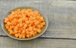 Brown bowl with diced carrots on wooden table, closeup. Brown bowl with diced carrots on wooden table Royalty Free Stock Photo