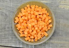 Brown bowl with diced carrots on wooden table, closeup. Brown bowl with diced carrots on wooden table Stock Photography