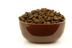 A brown bowl filled with coffee beans Royalty Free Stock Image