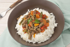 A brown bowl of white rice with stir fry beef with Royalty Free Stock Image