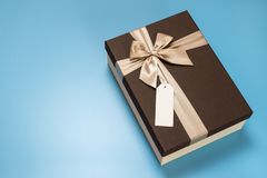 Brown box with golden ribbon and a blank label attached with copy space royalty free stock photography