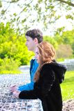 A brown boy and a pretty girl with long red hair side by side in profile in nature stock images