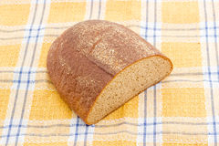 Brown bread on a checkered tablecloth. Stock Image