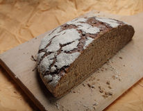 Brown bread on chopping board. Bread rustic style half on chopping board Stock Image