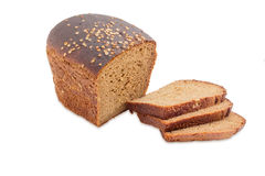 Brown bread with coriander on a light background. Part loaf of brown bread from rye and wheat flour with coriander and several slices of bread on a light Stock Photography