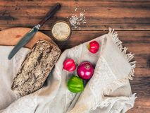 Brown bread with cracked crust wrapped in a cloth from a rough fabric. Still life of salt, vegetables, knife and cloth. On wood background. Composition in a Stock Image