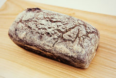 Brown bread dusted the flora on a beautiful bright wooden board. Royalty Free Stock Photos