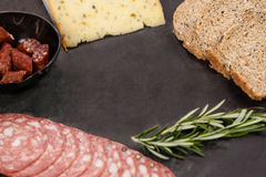 Brown bread, dutch gouda cheese, rosemary and meat on slate board Stock Image
