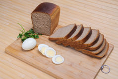 Brown bread and egg. Sliced brown bread Darnitskiy and egg on a cutting board Royalty Free Stock Photo
