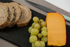 Brown bread, grapes and gouda cheese on slate board Stock Photography