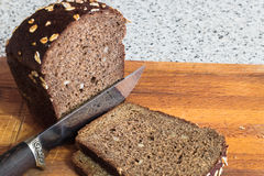 The brown bread. The knife cuts off a piece of brown bread Stock Photos