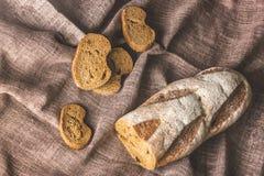 Brown bread in a linen napkin. Brown bread cut into pieces in a brown linen napkin Stock Photos