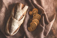 Brown bread in a linen napkin. Brown bread cut into pieces in a brown linen napkin Stock Photography
