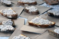 Brown bread pieces covered by spread on paper pieces Stock Photos