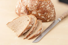 Brown bread slices. Horizontal, close-up image of Brown bread slices on creamy background with bread knife and loaf Royalty Free Stock Photography