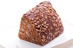 Brown bread with sunflower seeds on a white plate. Brown bread with sunwlower seeds on a white plate, shot on white background Royalty Free Stock Photo