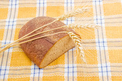 Brown bread and three spikes on a checkered tablecloth. Royalty Free Stock Photos