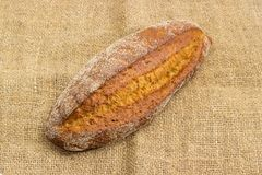Brown bread with the whole sprouted wheat grains on sackcloth. Whole oval loaf of the wheat and rye sprouted bread with added whole sprouted wheat grains, rye Stock Photo