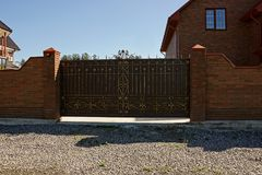 Brown brick fence and closed gates with a private house near the road. Closed private iron gates and a brown brick fence in front of a private house Royalty Free Stock Photo