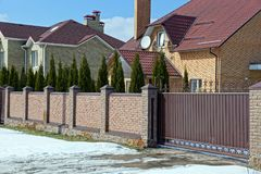 Brown brick fence and iron closed gates on the street near the road in the snow. Part brown brick fence and iron closed gates on the street near the road in the royalty free stock photo