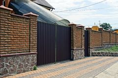 Brown brick fence and iron gates in front of the house Stock Photos