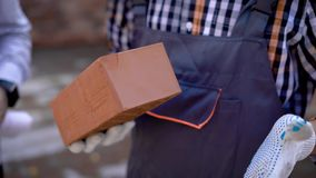 Brown brick in hands of builder. Close up view of builder hands stock video