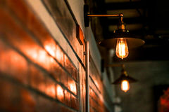 Brown brick wall and light bulb. House indoor dark electricity metal furniture hotel switch yellow decor nobody bright electric object with sconce apartment Stock Photo