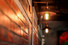 Brown brick wall and light bulb. House indoor dark electricity metal furniture hotel switch yellow decor nobody bright electric object with sconce apartment Stock Images