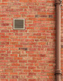 Brown Brick Wall with Vent and Old Pipe. Copy space Stock Images