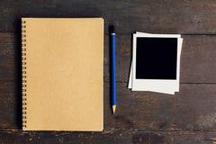 Brown-Buch und -bleistift mit Rahmenfoto auf hölzernem Tabellenhintergrund Stockfotos