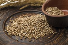 Buckwheat in a clay bowl. Brown buckwheat in a clay pot on the table Royalty Free Stock Images