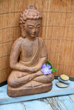 Brown Buddha statue with bamboo reed background Royalty Free Stock Photos