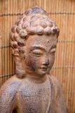 Brown Buddha statue with flowers  Royalty Free Stock Images