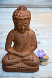 Brown Buddha statue with flowers and zen stones Stock Photo