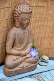 Brown Buddha statue with flowers and zen stones Stock Photos