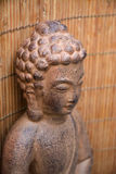 Brown Buddha statue with flowers and zen stones Stock Image