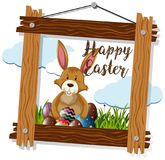 Brown bunny and eggs in wooden frame Royalty Free Stock Photo