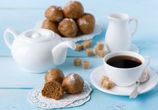 Brown buns on blue wooden table with coffee cup. Sugar, coffee pot and milk jug Royalty Free Stock Photography