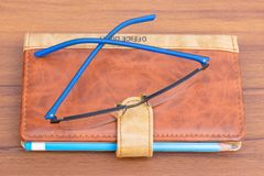 Brown business diary with ball pen and specks lying on wooden table. Brown business offiice diary with ball pen and glass on a light wooden background stock image