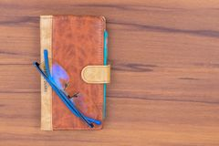 Brown business diary with ball pen and specks lying on wooden table. Brown business offiice diary with ball pen and glass on a light wooden background royalty free stock photography