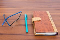 Brown business diary with ball pen and specks lying on wooden table. Brown business offiice diary with ball pen and glass on a light wooden background royalty free stock photos