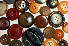 Brown Buttons. Assorted round buttons in shades of brown on white background royalty free stock photography