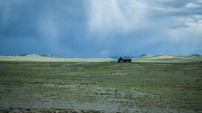 Brown Cabin on the Green Fields Below the Blue Sky Stock Photography