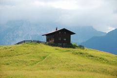 Brown cabin on hill in Alps. Brown cabin surrounded by wooden fence on top of green hill in Alps on summer afternoon stock image
