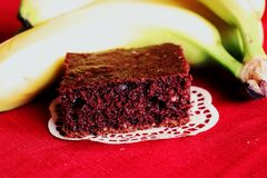 The brown cake on paper pad with yellow bananas. Tablecloth Stock Image
