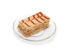 Brown cake on plate. Brown cake on a transparent plate isolated on white background Stock Photo